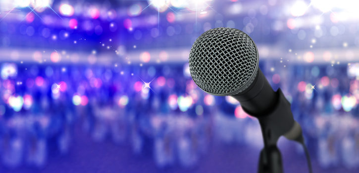 Close up microphone  on stage in concert hall or conference ball room.